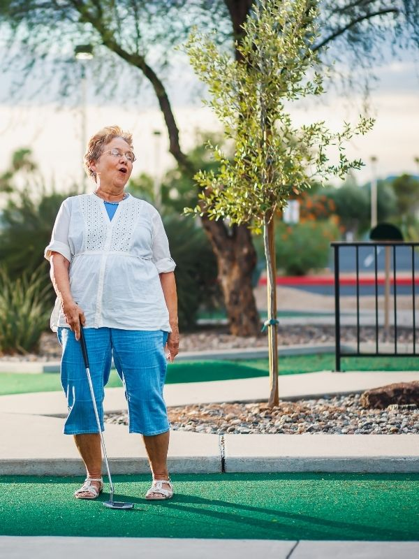 Retiree on synthetic putting green field